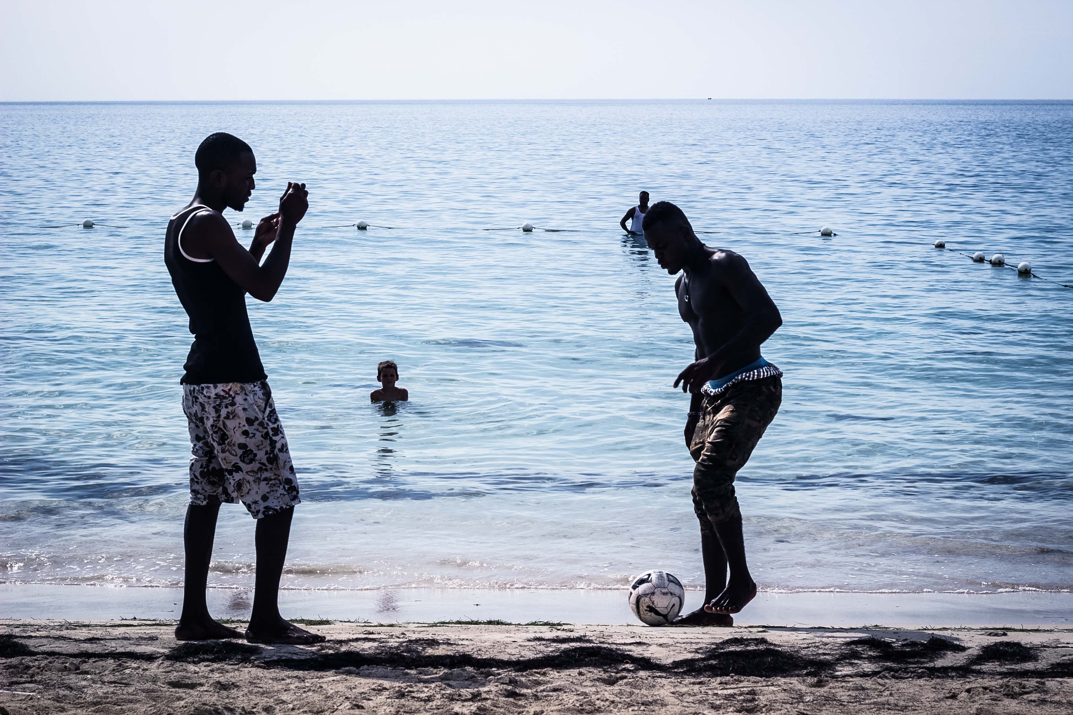 men play football on a beach in Negrill