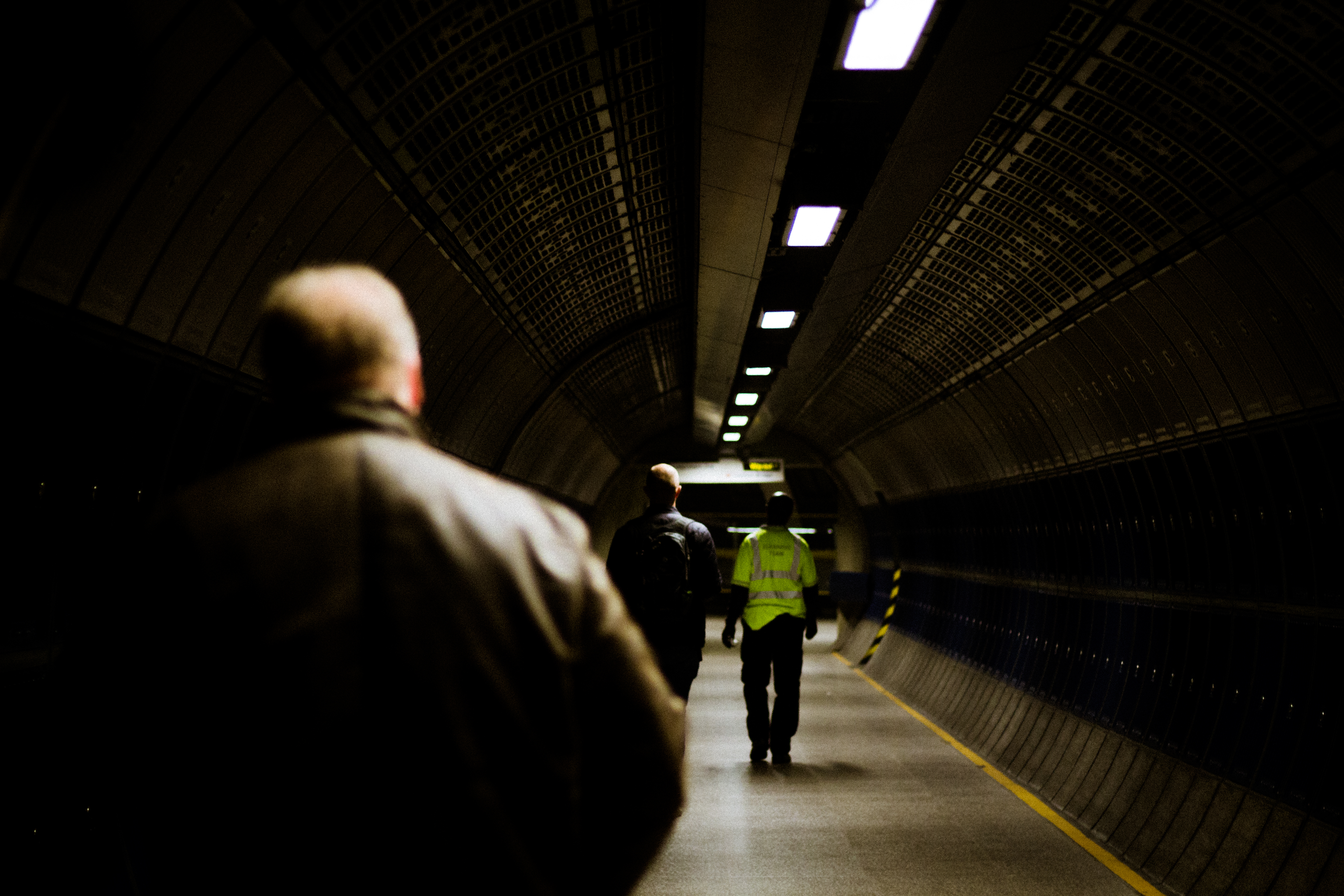 three men walk towards a platform at London Bridge underground